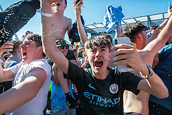 © Licensed to London News Pictures . 12/05/2019. Manchester , UK . Manchester City supporters celebrate after watching the club's Premier League match at Brighton on a big screen in City Square at the Etihad Stadium in which they beat Brighton and won the title for the second time in a row . Photo credit : Joel Goodman/LNP