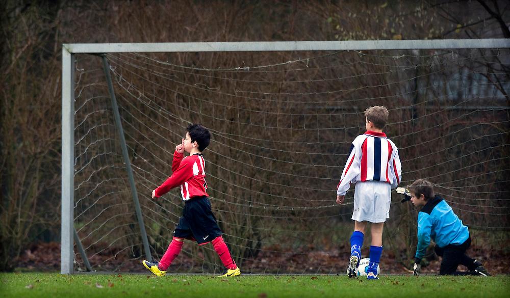 Nederland, Best, 06-12-2008.<br /> Voetbal, Nationaal, Junioren.<br /> Wilhelmina Boys E1 - PSV E1.<br /> Een PSV-spelertje heeft gescoord en laat met het bekende gebaar met de vinger voor de mond, de tegenstanders achter.<br /> Foto: Klaas Jan van der Weij