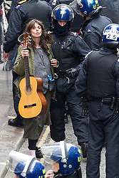 © Licensed to London News Pictures . 11/06/2013 . London , UK . Police lead away a woman with a guitar from inside after cutting their way in with an angle grinder . Police surround a former police station on 40 Beak Street , Soho this morning (11th June) . The site has been occupied by organisers of today's Stop G8 anti capitalist protests . Demonstrations in London today (Tuesday 11th June 2013) ahead of Britain hosting the 39th G8 summit on 17th/18th June at the Lough Erne Resort , County Fermanagh , Northern Ireland , next week . Photo credit : Joel Goodman/LNP