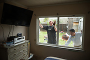 Cory Fessenmeyer, left, and Ruben Reyes install a new window on a Milpitas house during the Our Community Church and Rebuilding Together partnered event on Earth Day in Milpitas, California, on April 22, 2017. (Stan Olszewski/SOSKIphoto)