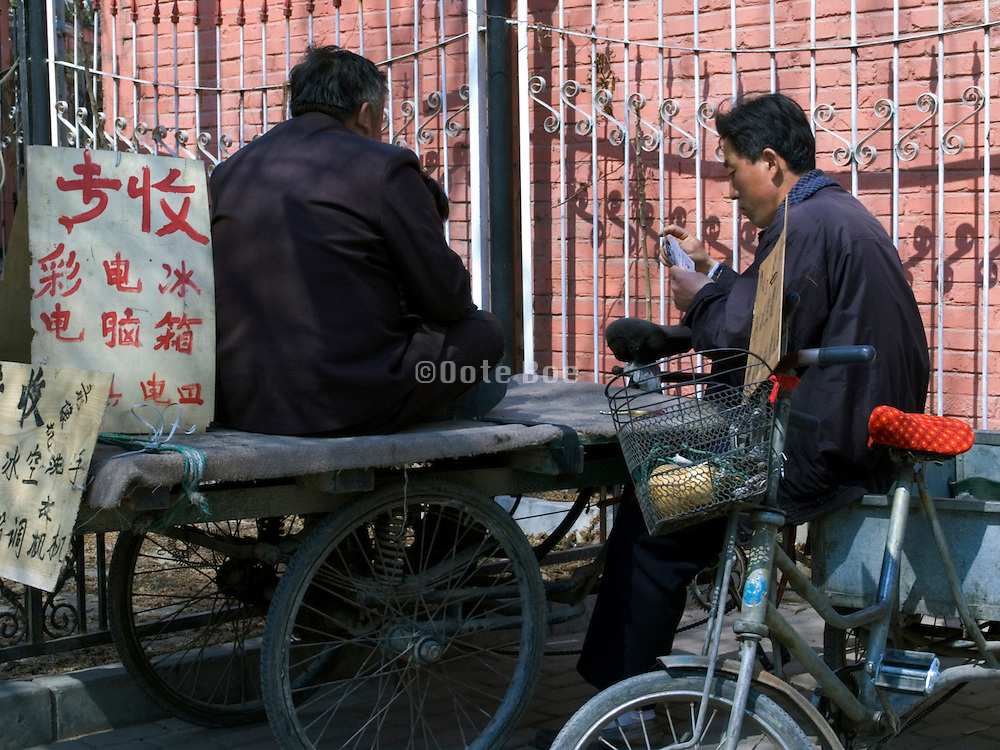 two men playing cards while waiting for a job Beijing China