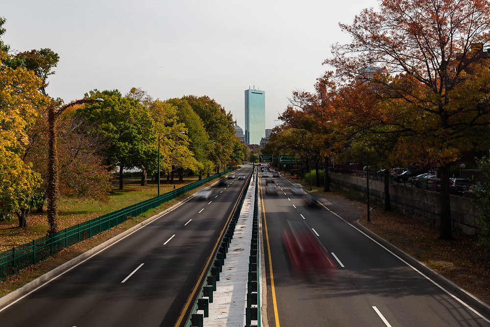 Car traffic driving along Storrow Drive on an autumn afternoon in Boston.