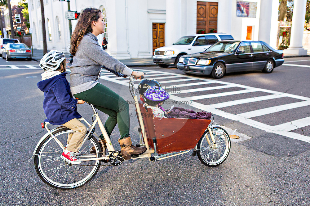 A women rides three children on her cargo bicycle known as a bakfiets in Charleston, South Carolina.