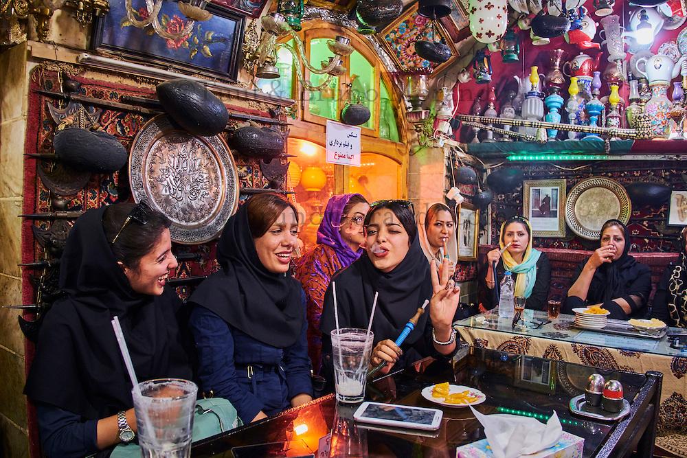 Iran, province d'Ispahan, Ispahan, maison de thé Azadegan, jeune femmes fumant du narguilé // Iran, Isfahan, Azadegan teahouse, young women smoking a water pipe
