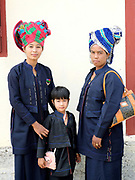 Portrait of two PaO ethnic minority women and a young girl at the PaO National Day on 24th March 2016 in Kayah State, Myanmar. The PaO origin story states that they are derived from a shaman, Zawgyu, and a female dragon so the women fashion their turban to resemble a dragons head