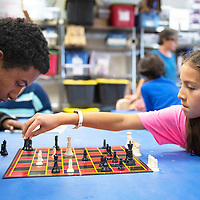 Catherine Denetclaw, 9, right, takes her turn against Isaiah McSweeney, 17, in a chess match Wednesday, May 22 during Chess Club at the Octavia Fellin Public Library Children's Branch.