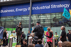 London, UK. 26th August, 2021. Stop HS2 activist Rollie addresses activists from Extinction Rebellion, Stop HS2, XR Roads Rebellion and Paid to Pollute outside the Department for Business, Energy and Industrial Strategy (BEIS) following the Stop The Harm march on the fourth day of Impossible Rebellion protests. Extinction Rebellion are calling on the UK government to cease all new fossil fuel investment with immediate effect.