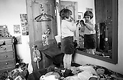 As her younger brother makes mischief in the background, 4 year-old girl looks at her appearence in front of a large mirror in her own bedroom at home in south London.
