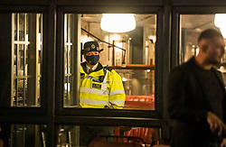 © Licensed to London News Pictures. 25/09/2020. London, UK. A police officer enters a bar on Portobello Road in Notting Hill to ask members of the public to leave, at 10pm when a curfew comes in to place as part of new restrictions intended to prevent the spread of COVID-19. Photo credit: Ben Cawthra/LNP
