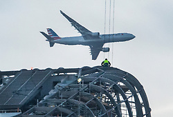© Licensed to London News Pictures. 19/12/2017. London, UK. A passenger plane heading for Heathrow passes a construction worker braving the cold as he works at the top of 'One Blackfriars' a sky scraper next to the River Thames - as parts of the UK are hit by fog and frost with travel disruption expected. The 52 storey apartment block began construction in 2013 and is 535 feet tall. Photo credit: Peter Macdiarmid/LNP