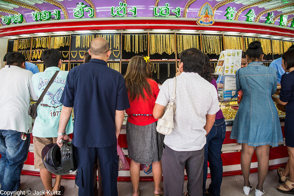 """06 MARCH 2013 - BANGKOK, THAILAND:  People crowd around a counter in a gold shop in Bangkok. Thailand's economic expansion since the 1970 has dramatically reduced both the amount of poverty and the severity of poverty in Thailand. At the same time, the gap between the very rich in Thailand and the very poor has grown so that income disparity is greater now than it was in 1970. Thailand scores .42 on the """"Ginni Index"""" which measures income disparity on a scale of 0 (perfect income equality) to 1 (absolute inequality in which one person owns everything). Sweden has the best Ginni score (.23), Thailand's score is slightly better than the US score of .45.  PHOTO BY JACK KURTZ"""