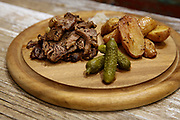 sliced Grilled beefsteak meal on wooden platter with baked potatoes