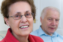 Older couple at home smiling,