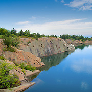 The granite quarry at Halibut Point in Rockport, MA was operated from about 1840 to 1920. Now part of a State Park, its reflecting fresh waters blend with the hues of the Atlantic beyond the line of trees.