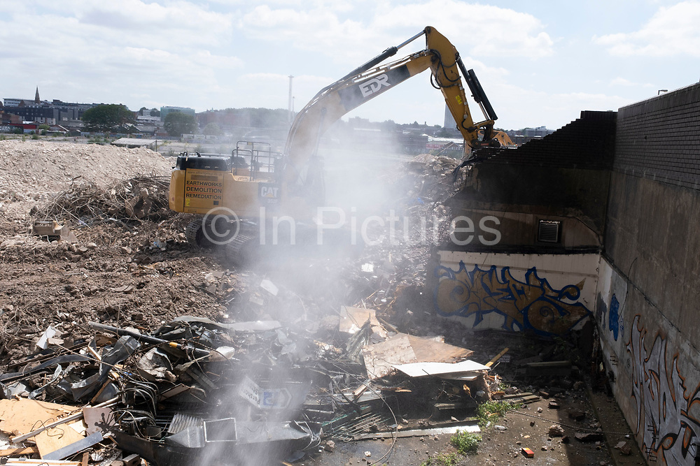 Powerful water spray dampening down the area where a digger working on tearing down and moving debris and rubble from an old multi storey car park as part of a development / redevelopment of old builindgs in the city centre on 14th July 2021 in Birmingham, United Kingdom. The city is under a long term and major redevelopment, with much of its industrial past being demolished and made into new flats for residential homes, as part of the Big City Plan.