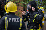 London Fire Brigade (LFB) firefighters attend a local minor roof fire in Herne Hill, south London. One fireman wearing a face mask and hood is equipped for BA (Breathing Apparatus) necessary to a burning building. The man adjusts straps and regulates his oxygen supply so breathing is possible inside a smoking environment.