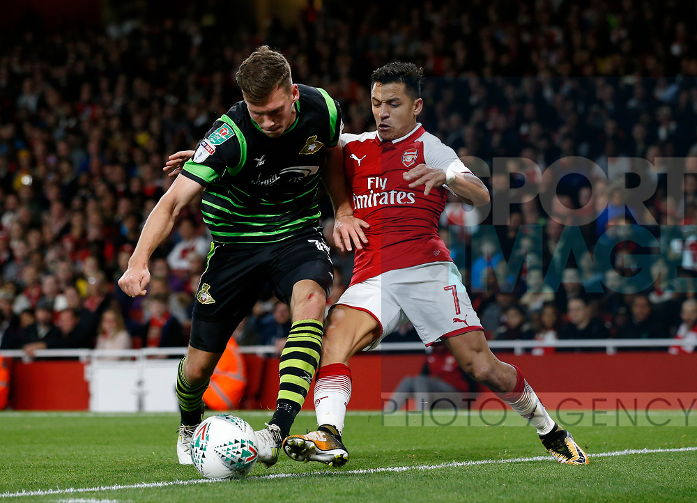 Arsenal's Alexis Sanchez tussles with Doncaster's Joe Wright during the Carabao Cup Third Round match at the Emirates Stadium, London. Picture date 20th September 2017. Picture credit should read: David Klein/Sportimage