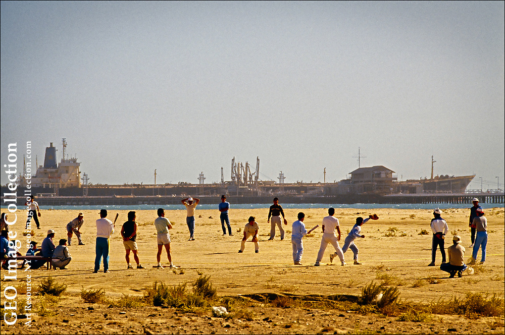 With a giant super-tanker in the background, Japanese workers play baseball at the North Pier Oil Terminal in Kuwait City on the Persian Gulf. The North Pier terminal is part of the Mina Al Ahmadi, the principal Kuwaiti port for the export of oil and gas and owned by the state-run Kuwait Oil Company.