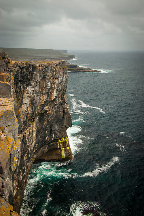 The imposing view from  Dun Aengus Stone Fort, Inishmore, the Aran Islands, off Ireland's west coast. The fort is preched on a windswept 100-metre high cliff above the Atlantic waves. Thought to date to the 2nd century BC,  it is surrounded by cheval de frise defences.