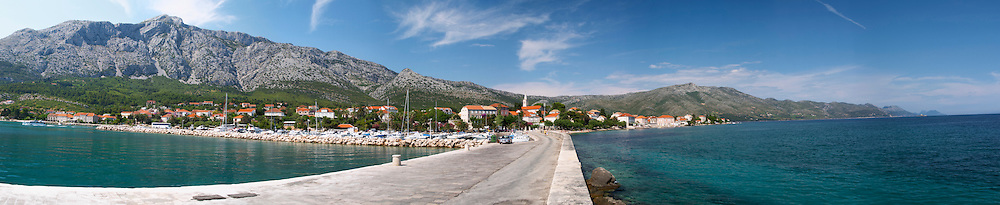 A very wide panorama of the harbour jetty pier and the village and beach, the massive mountains in the background Mount Sveti Ilija mountain. Orebic town, holiday resort on the south coast of the Peljesac peninsula. Orebic town. Peljesac peninsula. Dalmatian Coast, Croatia, Europe.