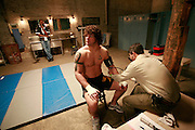 An MMA fighter is checked out by the fight doctor before the fight in the MMA locker room.
