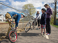 Myles Chase from MC Cycle puts some air in Jack Randall's tires while riding with Katie Riendeau and Sarah Gagnon from Pleasant Street School on Monday afternoon.  (Karen Bobotas/for the Laconia Daily Sun)