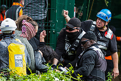 Denham, UK. 7th September, 2020. National Eviction Team enforcement agents grapple with activists from HS2 Rebellion seeking to prevent or delay tree cutting in conjunction with the HS2 high-speed rail link in Denham Country Park. Anti-HS2 activists continue to campaign and take direct action against the controversial £106bn project for which the construction phase was announced on 4th September from a series of protection camps based along the route of the line between London and Birmingham.
