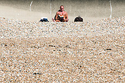 © Licensed to London News Pictures. 03/07/2014. Bognor Regis, UK . A man reads a book in the sunshine. People enjoy the hot sunny weather at the seaside resort of Bognor Regis today 3rd July 2014. Forecasters are predicting it to be the hottest day of 2014 so far. Photo credit : Stephen Simpson/LNP