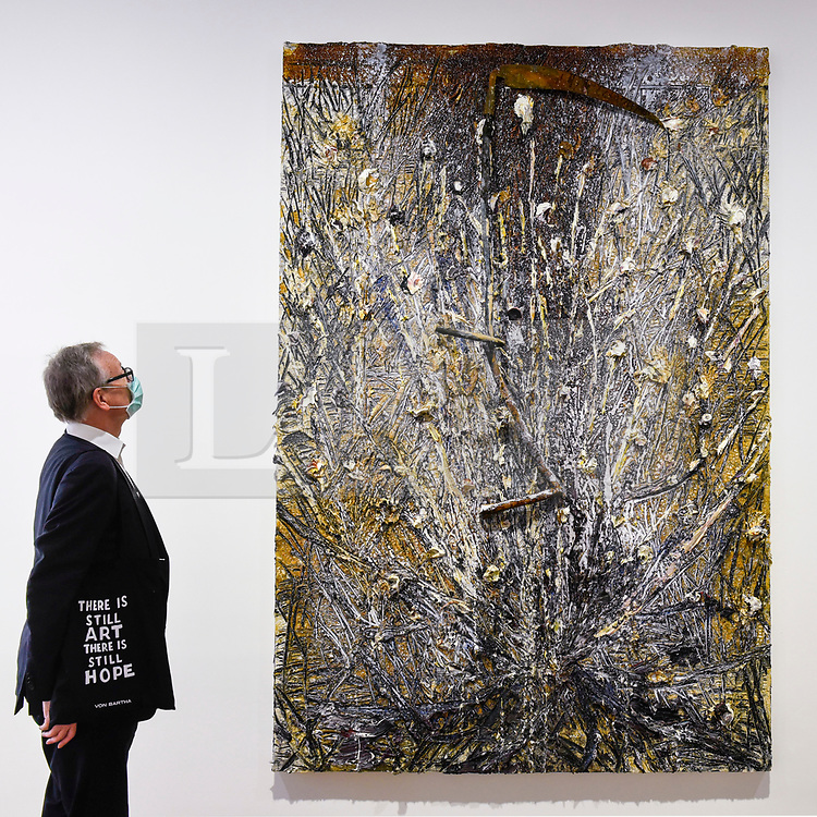 """© Licensed to London News Pictures. 16/06/2020. LONDON, UK. A visitor, wearing a facemask and carrying a bag with a topical message, views """"Memento Mori"""", 2020, by Anselm Kiefer on the opening day of a new exhibition """"Art Basel at Ely House"""" taking place at Galerie Thaddaeus Ropac in Mayfair.  The commercial gallery has implemented social distancing guidelines for visitors for its reopening after coronavirus pandemic lockdown restrictions were relaxed by the UK government.  The exhibition runs 16 June to 31 July 2020.  Photo credit: Stephen Chung/LNP"""