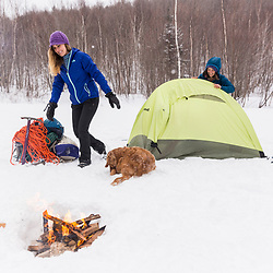 Two women set up camp while winter camping in New Hampshire's White Mountains. Randolph Community Forest.
