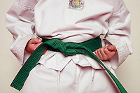 7 February 2008: 7 year old Aaron Stafford wearing a green belt. Tae Kwon Do student athletes in motion. Young kids practicing Taekwondo at the USA Black Belt Academy in Huntington  Beach, CA. Tae Kwon Do is a Korean Martial Art discipline that trains the body and mind.  It is global sport that is an official Olympic sport. ? Background Retouched *