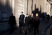 Scene in the City of London in the afternoon winter light as city workers and others walk past the Bank of England in the centre of London's main financial district.