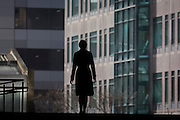Single silhouette of woman walking through the Broadgate corporate offices development in the City of London.