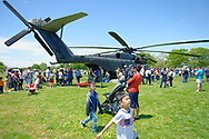 East Meadow, New York, USA. May 25, 2019. Families line up to go inside U.S. Navy MH53-E helicopter from the rear, at the U.S. Navy hosted aviation event, as part of Fleet Week, on Memorial Day Weekend at Eisenhower Park on Long Island. Visitors could speak with members of Command HM14, Helicopter Mine countermeasures Squadron 14, which has a Korea deployment mine sweeping.  MH-53E does long range minesweeping, and carries heavy loads and transports and picks up things for the Navy.