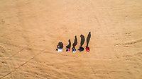 Aerial view of friends imitating the human evolution with their shadows in the Sharjah desert, U.A.E.