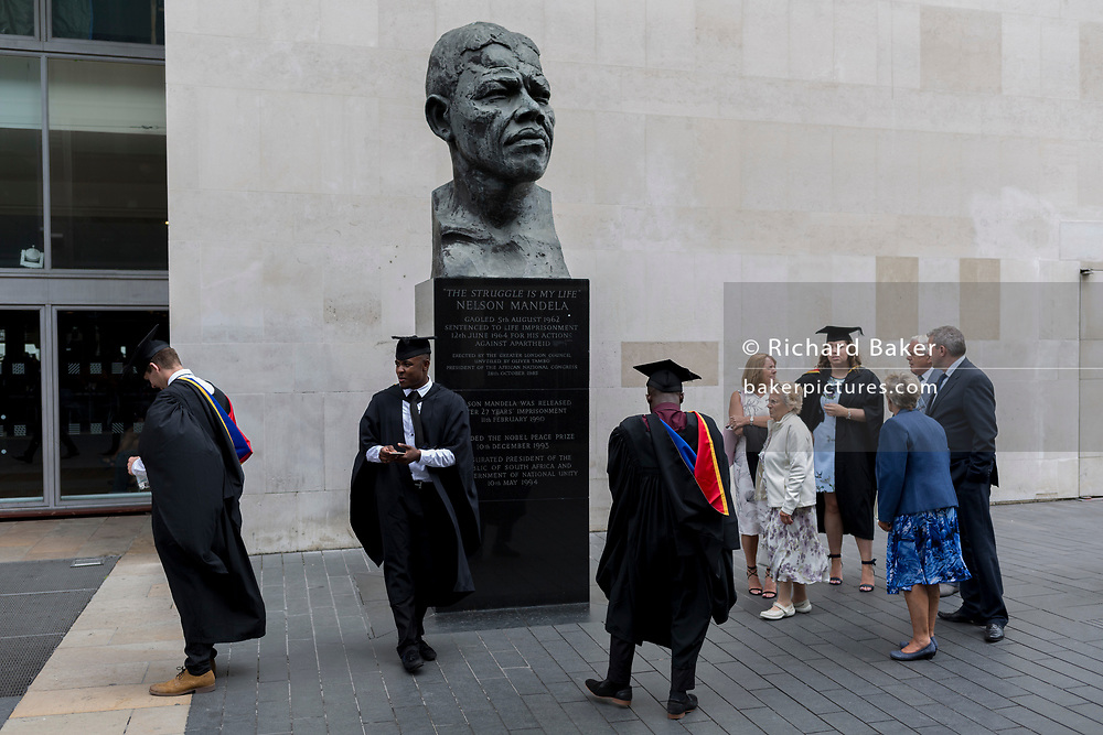 Young black graduates stand with a caucasian friend beneath the bust of Nelson Mandela after their graduation eremony, in celebration of their university academic achievement, outside the Festival Hall, on 20th July 2017, on the Southbank, London, England.