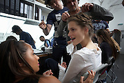 "Make-up and hair stylists ready a model before the couturier Margaret Howell's Fashion Week show in the company's retail flagship and design studio at 34 Wigmore Street, Central London England. The young beauty has her lips dabbed with tissue to stop her lipstick from smudging. The hairdresser pins her braided hair in a whirl on her head and in the background, other freelance stylists busy themselves in the frantically busy room to get the show on the road. Howell is one of Britain's more understated of couture brands alongside more flamboyant personalities. Howell admits to being ""inspired by the methods by which something is made .. enjoying the tactile quality of natural fabrics such as tweeds, linen and cotton in a relaxed, natural and lived in look."""