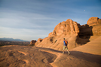 Young man hiking in Arches National Park near Moab, Utah.