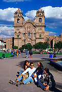 Young people gather in front of La Compania Church, Plaza de Armas  square in Cuzco, the ancient capital of the Inca Empire, Peru, South America