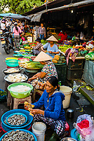 Women selling produce at outdoor market, Central Market, Hoi An, Vietnam.