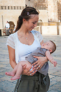 A Jewish mother visiting from Luxembourg holds her child at the Western Wall Plaza in Jerusalem on October 20, 2010
