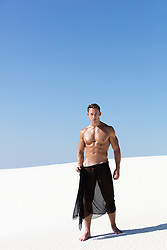 shirtless hot man with black fabric in the desert