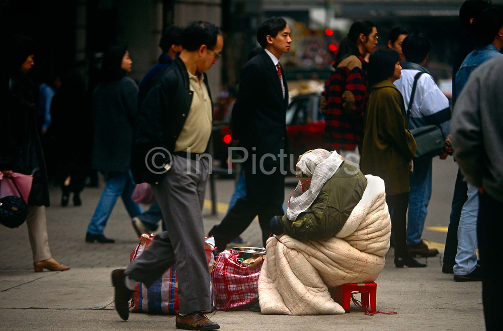 Passers-by ignore a destitute bag lady in a Hong Kong's Tsim Sha Tsui street on the Kowloon side. The poor woman sits amid the bustle and crowds of a capitalist population obsessed with wealth and prosperity, she is alone in a material world. Bent over with shame and poverty, the lady is shrouded in a sleeping bag with all her worldly possessions at her feet. Unconcerned, the rest of the Chinese shoppers and commuters simply pass-by on their way to achieve yet more success in this former British-ruled colony that was ceded back to China in 1997.