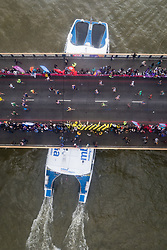 © Licensed to London News Pictures. 23/04/2017. LONDON, UK.  Mass marathon runners on Tower Bridge as a boat passes under, seen from the glass walkway of Tower Bridge, as the runners reach the half way point.  Photo credit: Vickie Flores/LNP