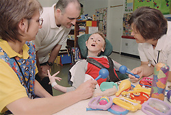 Young boy with Cerebral Palsy sitting in wheelchair with father; nursery assistant and patient assistant,