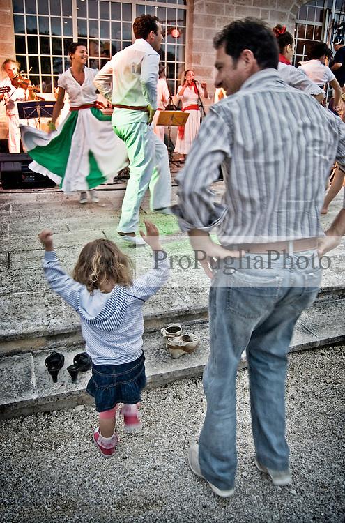 """Una piccola spettatrice con un adulto assistono in maniera coinvolgente allo spettacolo dei ballerini del gruppo musicale di Pizzica """"Arakne Mediterranea"""" durante un concerto a """"Castello Monaci"""" nei pressi di Salice Salentino in provincia di Lecce. 30/05/2010 (PH Gabriele Spedicato)..People dancing with the dancers of """"Arakne Mediterranea""""during the concert in """"Castello Monaci"""" near Salice Salentino, a Town in province of Lecce.30/05/2010 PH Gabriele Spedicato..La pizzica, o, detta nella sua forma più tradizionale pizzica pizzica, è una danza popolare attribuita oggi particolarmente al Salento, ma in realtà era praticata sino agli anni '70 del XX sec. in tutta la Puglia centro-meridionale e in Basilicata..Fa parte della grande famiglia delle tarantelle, come si usa chiamare quel variegato gruppo di danze diffuse dall'Età Moderna nell'Italia meridionale"""