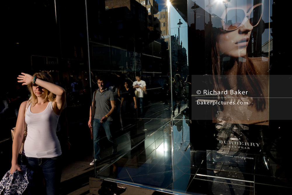 Shading her eyes from bright sun, a woman is near a poster girl for Burberry sunglasses they call Eyewear, in a London street. Burberry Group plc is a British luxury fashion house, manufacturing clothing, fragrance, and fashion accessories.