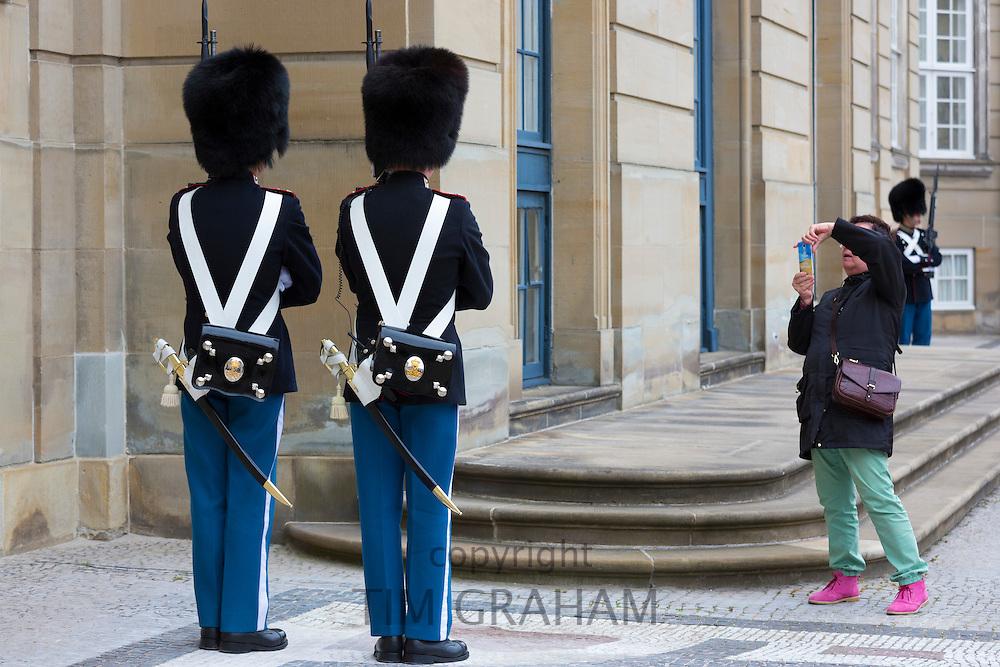 Tourist taking photograph of Royal Guard, in uniform at Royal Amalienborg Palace, Copenhagen, Denmark
