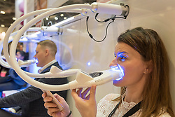 © Licensed to London News Pictures. 25/02/2019. LONDON, UK. Visitors try a teeth whitening product at Professional Beauty, the UK's largest beauty and spa trade show, taking place at Excel London in Docklands.  Photo credit: Stephen Chung/LNP
