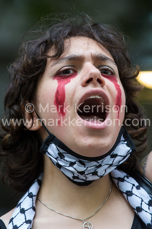 London, UK. 28th May, 2021. An activist from Palestine Action daubed with fake blood and wearing a keffiyeh face covering protests outside the UK headquarters of Elbit Systems, an Israel-based company developing technologies used for military applications including drones, precision guidance, surveillance and intruder-detection systems. The protest had been organised by Palestine Action against Elbit's presence in the UK and against British arms sales to and support for Israel.
